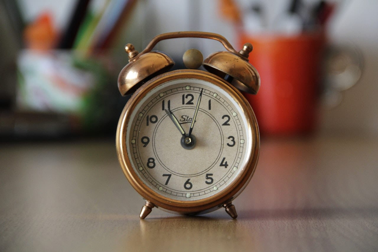 old-fashioned alarm clock sitting on desk.